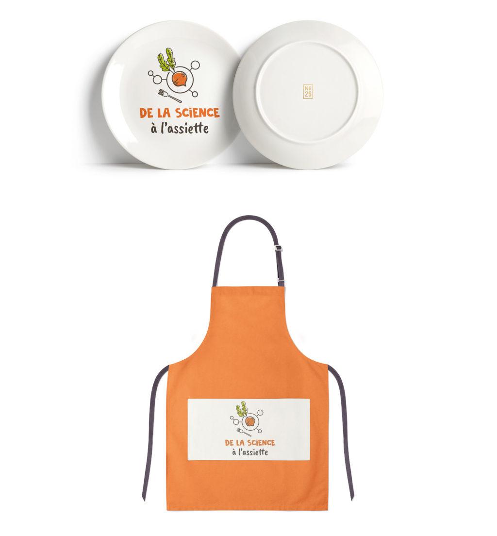 logo de la Science à l'Assiette imprimée sur des assiettes et sur un tablier de cuisine.